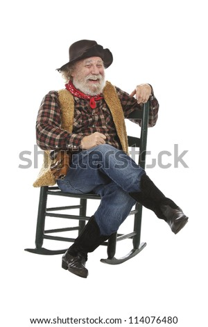 Classic Old West style laughing cowboy with felt hat, grey whiskers, revolver. He sits legs crossed in a rocking chair. Isolated on white, vertical, copy space. - stock photo