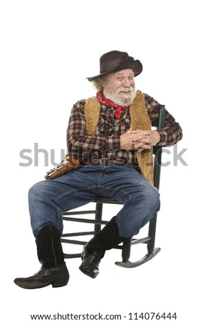 Classic old west style smiling cowboy with felt hat, grey whiskers, revolver. He sits in a rocking chair. Isolated on white, vertical, copy space. - stock photo