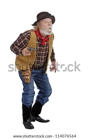Classic old west worried cowboy with felt hat, grey whiskers, revolver, stands ready with revolver. Isolated on white background, copy space, vertical. - stock photo