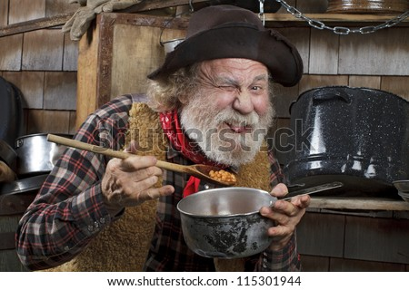 Classic old western style cowboy with felt hat, grey whiskers, red bandanna. He eats beans from a saucepan. Camp cookware and wood shingles in background. - stock photo