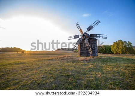classic old windmill in a field at sunset