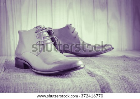 classic oxford shoes on wooden background, sepia tone, selective focus - stock photo