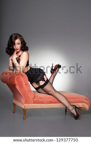 classic pinup in black lingerie on vintage chaise - stock photo