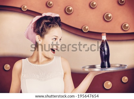 Classic portrait of a retro pinup girl holding food and drinks tray with soft drink bottle inside vintage cafeteria. 50s diner flashback - stock photo