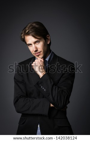 Classic profile portrait of a young business man wearing suit, isolated on gray background. - stock photo