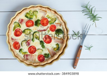 Classic quiche lorraine pie with broccoli, cheese and tomatoes in baking dish on white table background. Top view. - stock photo