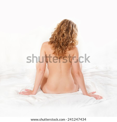 Classic rear view nude of a beautiful young woman sitting on white bed, beauty concept - stock photo