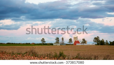 Classic red barn and other farm buildings beneath a dramatic evening  or morning sky with colorful clouds.  Bare farm field and autumn leaves in foreground. - stock photo