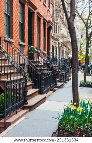 Classic red brick brownstone buildings with black iron railings in Greenwich Village, New York City. Upscale neighborhood. Street trees are planted with spring daffodils. - stock photo