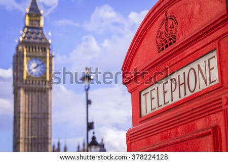 Classic red British telephone box with the Big Ben at background on a sunny afternoon with blue sky and clouds - London, UK - stock photo