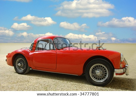 Classic red cabriolet on a background of the blue sky. - stock photo