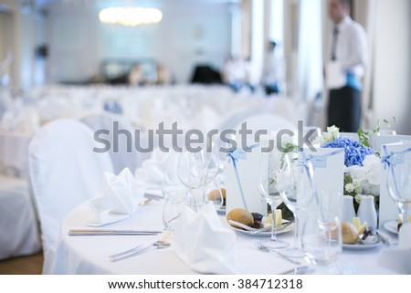 Classic restaurant/catering dinner tables setting, waiter on blurry background   - stock photo