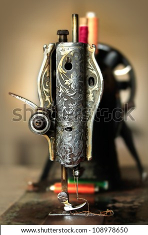 Classic retro style manual sewing machine ready for sewing work. The machine is old style made of metal with floral patterns - stock photo