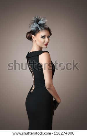 Classic retro style portrait of young beautiful brunette woman looking over shoulder - stock photo