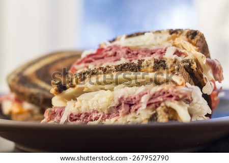 Classic reuben sandwich on pumpernickel swirl rye bread. A hearty meal with a side of pickle and chips - stock photo