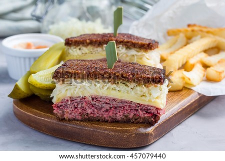 Classic reuben sandwich with corned beef, swiss cheese, sauerkraut and thousand island dressing on pumpernickel bread, served with dill pickle spear and potato chips, horizontal