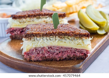 Classic reuben sandwich with corned beef, swiss cheese, sauerkraut and thousand island dressing on pumpernickel bread, served with dill pickle spear and potato chips, horizontal - stock photo
