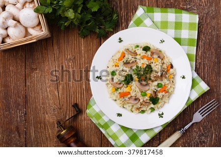 Classic Risotto with mushrooms and vegetables served on a white plate. - stock photo