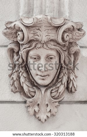 Classic roman head sculpture mounted on wall. - stock photo