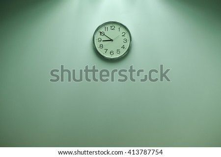 Classic round wall clock on the wall background.