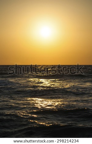Classic seascape with a view of the setting sun and waves