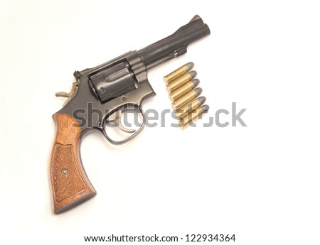 Classic six shooter gun with bullets. Profile of a .38 caliber handgun with wood grip. Six shiny bullets just below the gun. Isolated on a white background. - stock photo