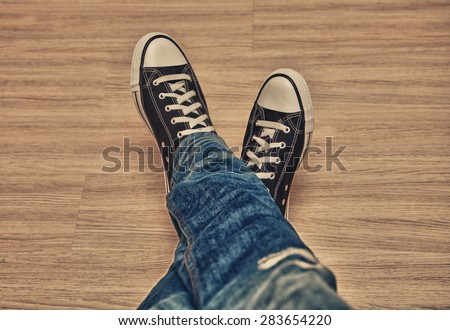classic sneakers black and white colors made of rubber and blue jeans. Youth Clothing unisex - stock photo
