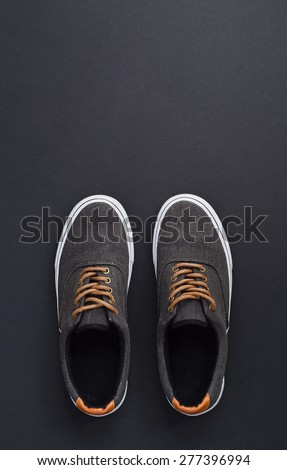Classic sneakers over dark black background, above view. Image with space for text or other design - stock photo