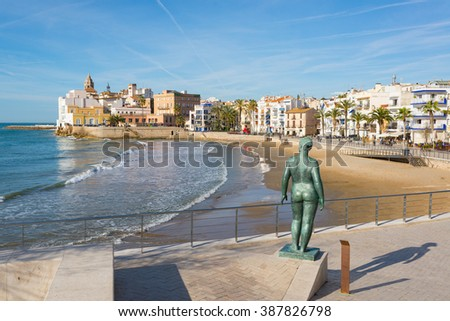 Classic statue of a naked woman shot from behind looking towards the town of Sitges, Barcellona, Spain