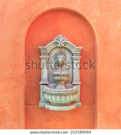classic stone carved lion heads on orange wall at home - stock photo