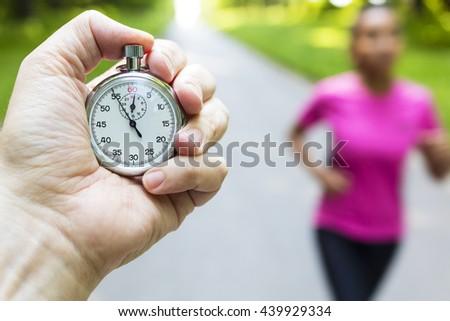Classic stopwatch timer and young woman in pink running or jogging being timed on a road in summer