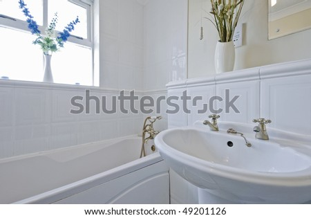 classic style bathroom with white ceramic suite and flowers - stock photo
