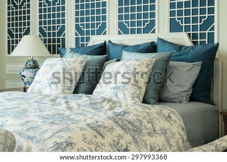 classic style bedroom with blue pillows and chinese lamp style on bedside table - stock photo