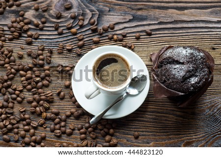 Classic style espresso shot with chip muffin and coffee beans on old wooden table. Top view. - stock photo