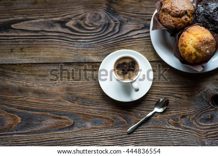 Classic style espresso shot with three chip muffin on old wooden table. - stock photo
