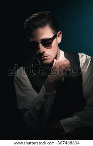 Classic stylish fashion man with sunglasses in waistcoat and tie. Greasy hair combed back. Against dark blue background. - stock photo