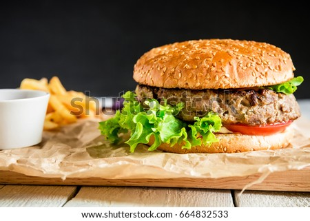 Classic tasty hamburger with tasty beef, sauce and french fries on dark background. American food