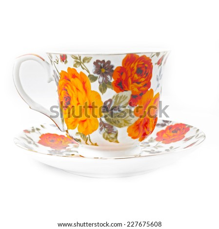 Classic tea cup with red and orange flowers  - stock photo