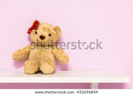 Classic teddy bear on shelf. Brown teddy on the pink background. - stock photo