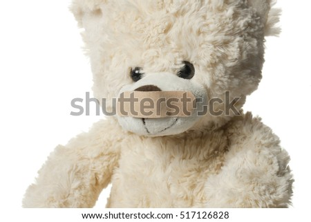 Classic teddy bear with bandages isolated on white background