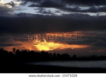 Classic tropical sunset with view of shoreline and waves breaking on beach. - stock photo