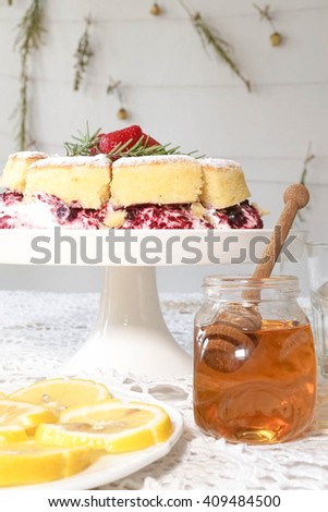 Classic victoria sponge cake, Honey and Lime served at the tea party, selective focus on the honey dropper - stock photo