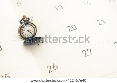 Classic vintage necklace watch on calendar date paper - concept time management - stock photo