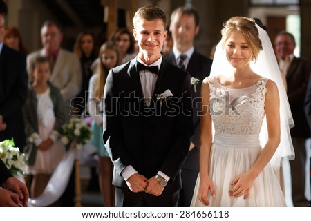 classic wedding ceremony of stylish young luxury bride and groom in the ancient old church - stock photo