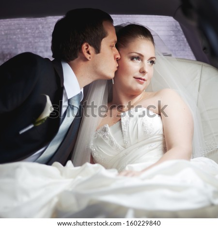 Classic wedding picture of a young couple in limo.