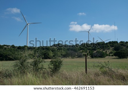 Classic Wind Turbine scene producing clean renewable energy Wind Farm in the distance as the background to a Texas hill country farm