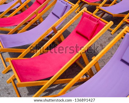 Classic wooden beach chairs in purple and pink