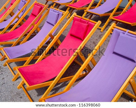 Classic wooden beach chairs in purple and pink background