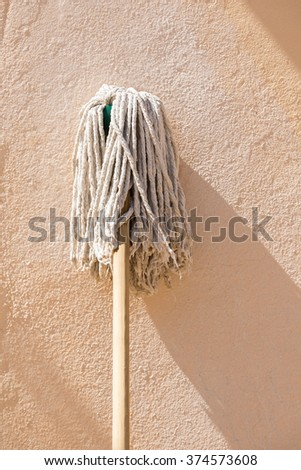 Classic wooden handled mop leaning up against a wall with room for text - stock photo