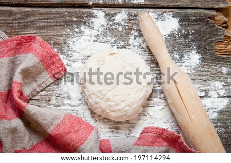 Classic wooden rolling pin with freshly prepared dough and dusting of flour on wooden background - stock photo